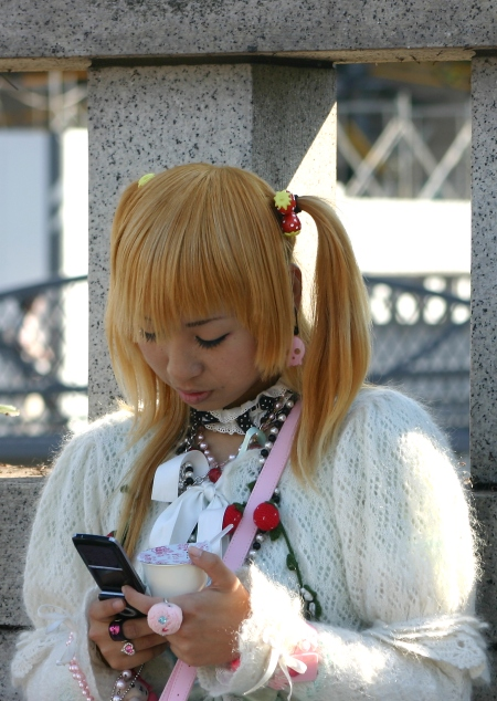 Harajuku girl checks her mobile phone